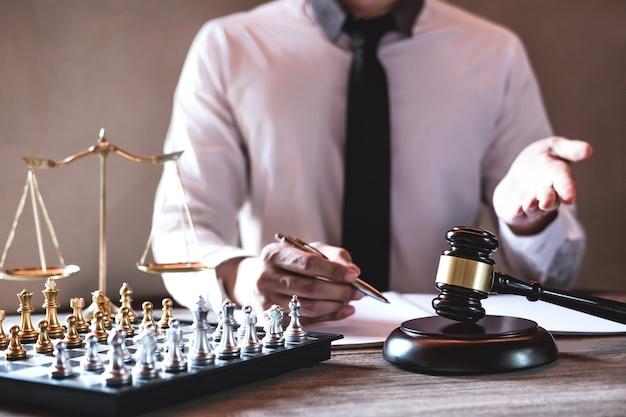 Professionelle männliche rechtsanwälte, die an dem gerichtssaal sitzt am tisch und unterzeichnet papiere mit hammer arbeiten Premium Fotos