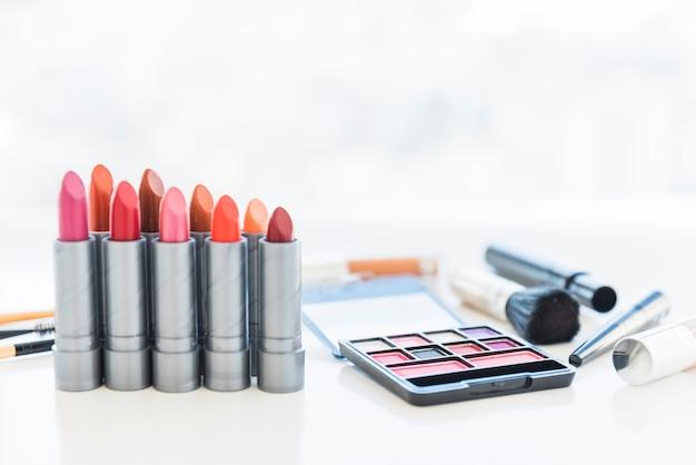 Professionelle make-up-tools mit einer palette von kosmetischen lidschatten und einer reihe von lippenstift-tönen Kostenlose Fotos
