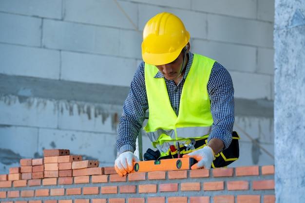 Professioneller arbeiter, der backsteinmauern mit zement baut Premium Fotos