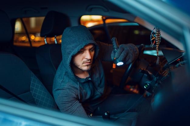 Professioneller autodieb mit taschenlampe, kriminellem lebensstil, diebstahl. Premium Fotos