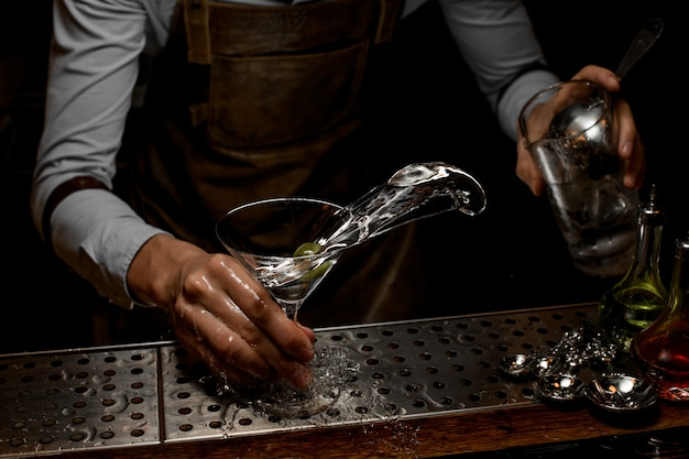 Professioneller barkeeper, der ein alkoholisches getränk im martini-glas mit einer olive mischt Premium Fotos