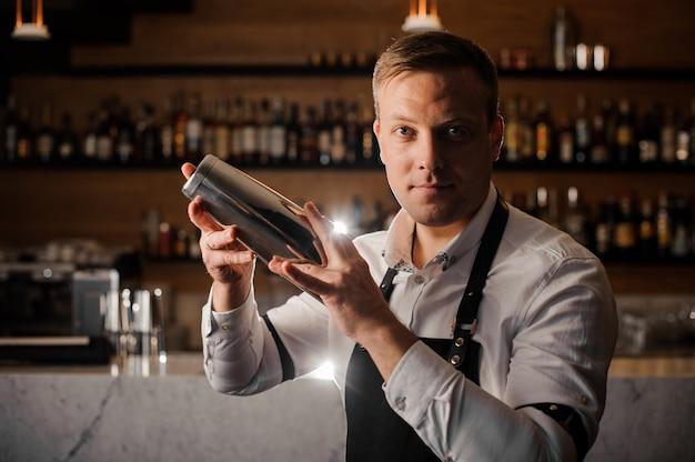 Professioneller barkeeper macht einen cocktail mit einem shaker Premium Fotos