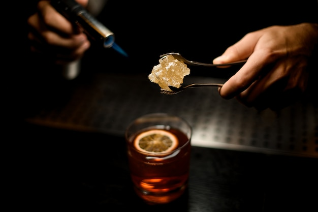 Professioneller barkeeper serviert ein braunes cocktail-karamell mit einem brenner über der zitronenscheibe Premium Fotos