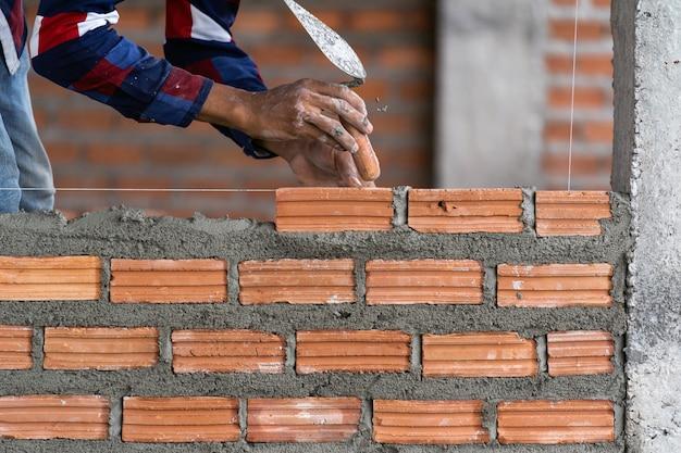 Professioneller bauarbeiter der nahaufnahmehand, der ziegelsteine im neuen industriestandort legt Premium Fotos