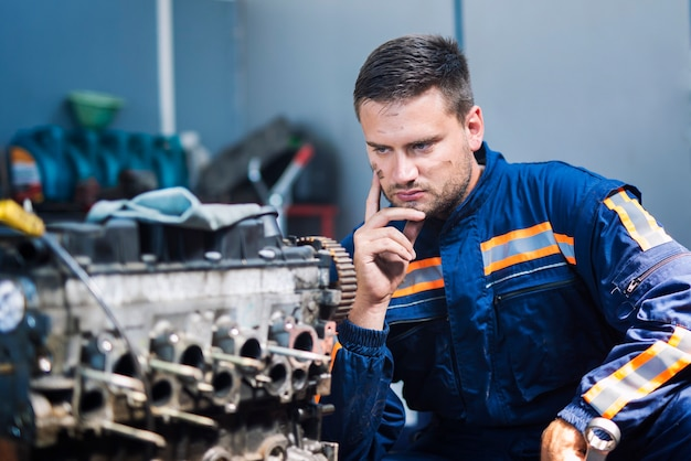 Professioneller erfahrener mechaniker-mechaniker in uniform, der über die lösung nachdenkt und den automotor in der mechanikerwerkstatt betrachtet Kostenlose Fotos