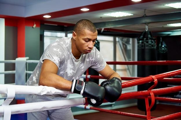 Professioneller junger boxer, der auf den seilen des ringes nach dem kampf stillsteht. Premium Fotos