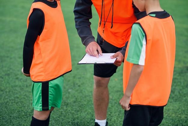 Professioneller junger fußballtrainer erklärt seinen spielern die strategie des fußballspiels Premium Fotos