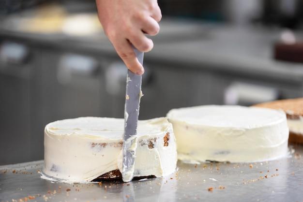 Professioneller konditor, der einen köstlichen kuchen in der konditorei macht. Premium Fotos