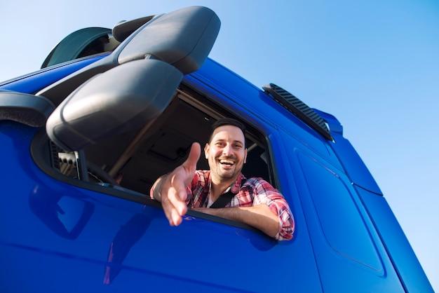 Professioneller lkw-fahrer mittleren alters, der in seiner fahrzeugkabine sitzt und neuen rekruten die hand schüttelt. Premium Fotos