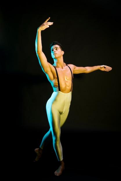 Professioneller männlicher balletttänzer, der im scheinwerfer durchführt Kostenlose Fotos