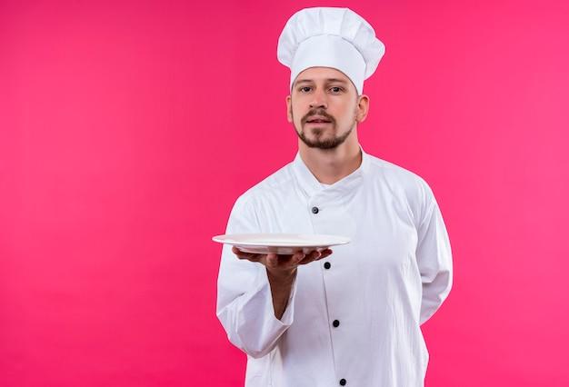 Professioneller männlicher koch kocht in der weißen uniform und im kochhut, der einen teller zeigt, der zuversichtlich steht, über rosa hintergrund zu stehen Kostenlose Fotos