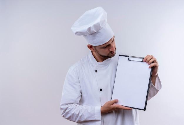 Professioneller männlicher koch kocht in der weißen uniform und im kochhut, der zwischenablage mit leeren seiten demonstriert, die über weißem hintergrund stehen Kostenlose Fotos