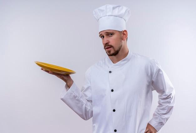 Professioneller männlicher kochkoch in der weißen uniform und im kochhut, der eine leere platte mit dem sicheren blick zeigt, der über weißem hintergrund steht Kostenlose Fotos