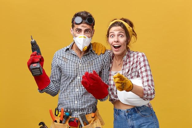 Professioneller männlicher techniker mit schutzbrille am kopf, schutzmaske und handschuhen, bohrmaschine mit werkzeuggürtel Kostenlose Fotos
