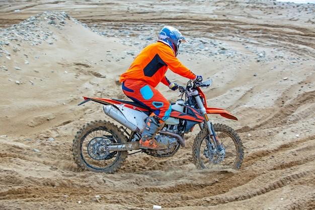 Professioneller motocross-motorradfahrer fährt über die straße. Premium Fotos