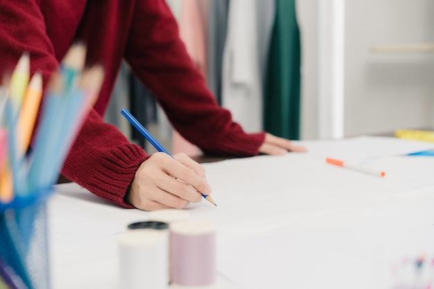 Professioneller schöner asiatischer weiblicher modedesigner, der mit gewebeskizzen arbeitet Kostenlose Fotos
