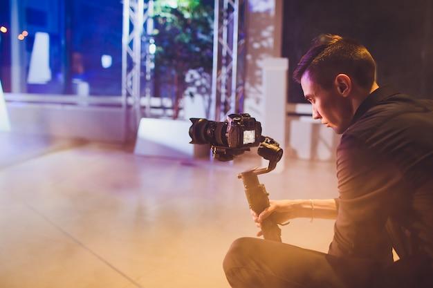 Professioneller videofilmer mit kamera auf 3-achsen-gimbal. videographer mit steadicam. pro-geräte helfen dabei, qualitativ hochwertige videos ohne verwackeln zu erstellen. Premium Fotos