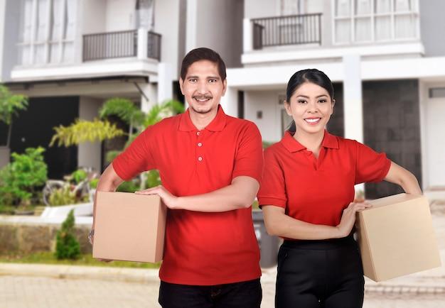 Professionelles asiatisches kurierteam mit dem roten hemd bereit, das paket zu liefern Premium Fotos