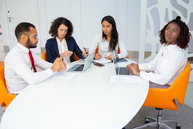 Professionelles business-team mit laptops und papieren Kostenlose Fotos