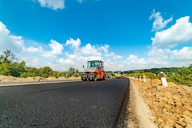 Professionelles equipment legt und richtet im sommer frischen asphalt auf der autobahn aus. Premium Fotos