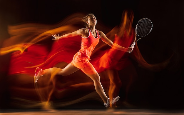 Professionelles weibliches tennisspielertraining lokalisiert auf schwarzem studiahintergrund in gemischtem licht. frau im sportanzug üben. Kostenlose Fotos