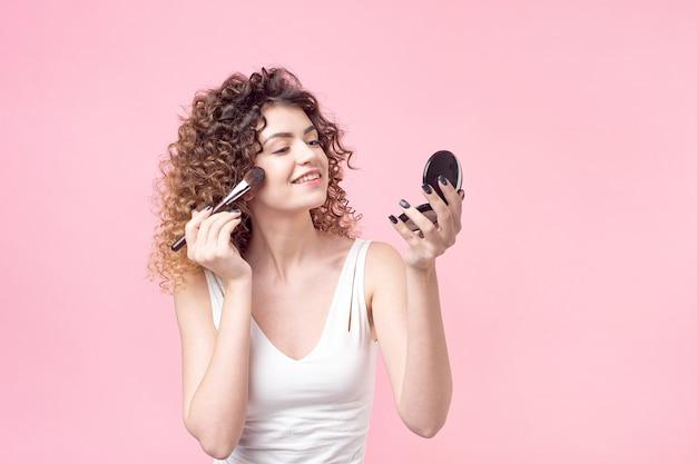 Profil der netten jungen frau steht mit handspiegel und pudert ihre nase Premium Fotos