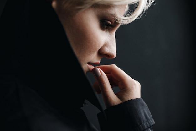 Profil einer schönen durchdachten frau, die ihre lippen berührt Kostenlose Fotos