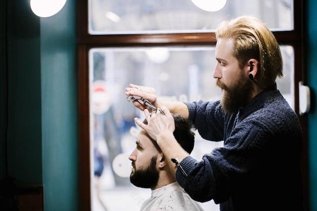 Profil von friseur schneide mannes haar Kostenlose Fotos