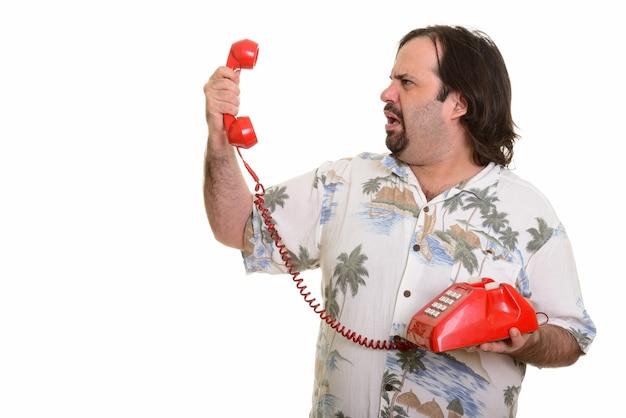 Profilansicht des fetten kaukasischen mannes, der altes telefon hält, das wütend schaut Premium Fotos