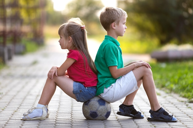 Profilieren sie porträt von zwei netten blonden kindern, von lächelndem jungen und von langhaarigem mädchen, die auf fußball sitzen. Premium Fotos