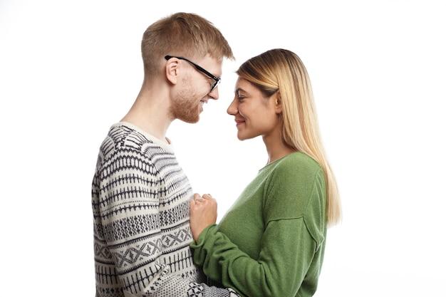 Profilporträt des glücklichen freudigen jungen mannes und der verliebten frau, die nahe beieinander stehen, sich umarmen und sprechen, fröhlich lächeln, sich entspannt und sorglos fühlen, gekleidet in stilvolle kleidung Kostenlose Fotos
