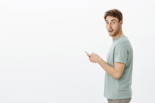 Profilporträt des verträumten gutaussehenden blonden mannes mit der borste, der sich vom smartphone-bildschirm während des messaging abwendet und auf kaffee im café wartet Kostenlose Fotos
