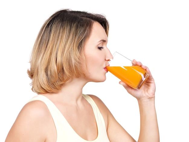 Profilporträt einer jungen frau trinkt orangensaft isoliert auf weiß. Kostenlose Fotos