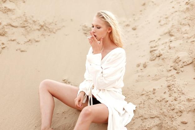 Profilporträt einer sexy jungen blonden frau im weißen hemd, rauchend sitzend auf dem sandboden. porträt im freien. Premium Fotos