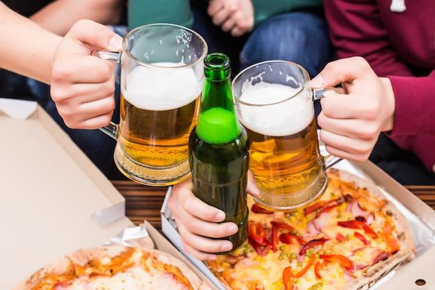 Prost. draufsicht auf männer mit gläsern bier und pizza Kostenlose Fotos