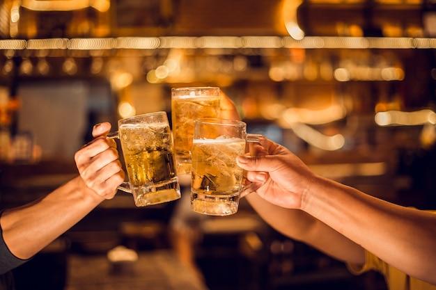 Prost! gruppe, bierkrug, junge männer brauen biergläser, um ihren erfolg zu feiern. Premium Fotos