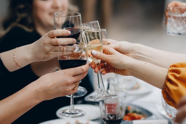 Prost! gruppe von leuten, die mit champagnerflöten mit hauptinnenraum jubeln Premium Fotos