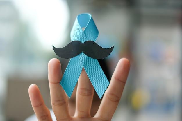 Prostatakrebs-bewusstsein, frauenhand, die hellblaues band hält Premium Fotos