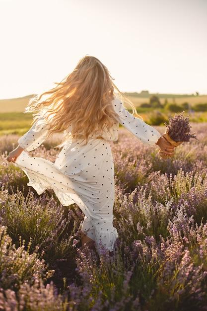 Provence frau, die im lavendelfeld entspannt. dame in einem weißen kleid. mädchen mit blumenstrauß. Kostenlose Fotos