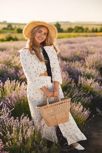 Provence frau, die im lavendelfeld entspannt. dame in einem weißen kleid. mädchen mit einem strohhut und einem korb. Kostenlose Fotos
