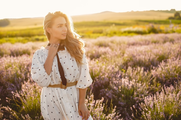 Provence frau, die im lavendelfeld entspannt. dame in einem weißen kleid. mädchen mit einem strohhut. Kostenlose Fotos
