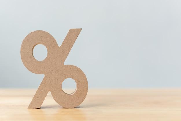 Prozentsatzzeichensymbolikone hölzern auf hölzerner tabelle Premium Fotos