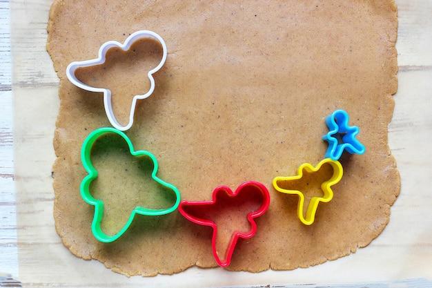Prozess der behandlung von lebkuchenmannplätzchen, benutzen roten lebkuchenmann-formausschnitt-lebkuchenteig auf backpapier um bunte ausstechformen auf weißem holztisch. ansicht von oben Kostenlose Fotos