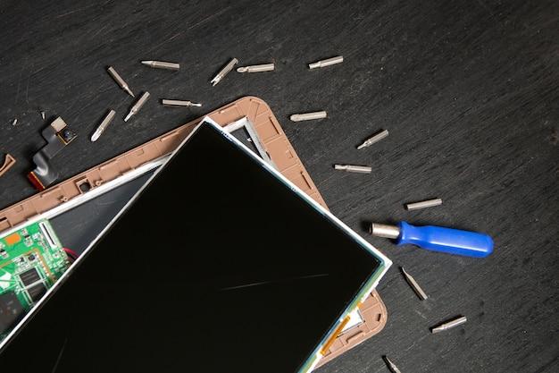 Prozess der gerätreparatur pc tablet nahe schraubenzieher und stückchen auf der schwarzen holzoberfläche auseinandergebaut Premium Fotos