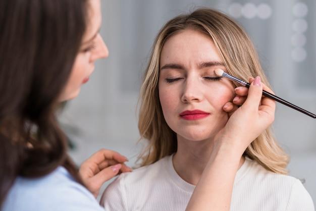 Prozess der make-up zur blonden schönen frau Kostenlose Fotos