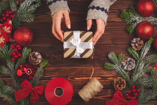 Prozess des verpackens von geschenken und des verzierens für weihnachtsfeiertage nah oben Premium Fotos