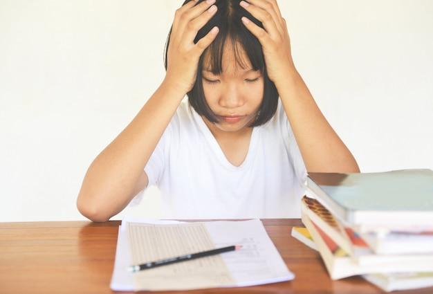 Prüfungsstress. ausbildung junge weibliche hochschule in der klasse, die kenntnisse nimmt und einen bleistift verwendet. Premium Fotos