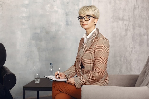 Psychologe mit brille sitzt auf einem stuhl im büro Kostenlose Fotos