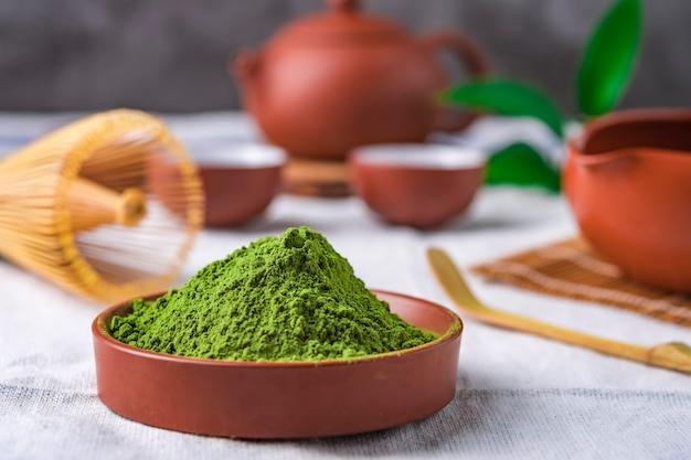Pulver des grünen tees mit blatt im keramischen teller auf dem tisch, japanischer draht wischen gemacht vom bambus für matcha teezeremonie Premium Fotos
