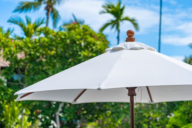 Punkt des selektiven fokus auf regenschirm mit kokosnusspalme auf dem hintergrund für feiertagsferien Kostenlose Fotos